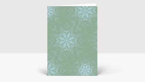 Weihnachtskarte Schneeflockenmuster blau auf grünem Grund